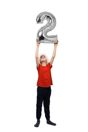 Boy in a Santa hat is holding a silver inflatable number 2 above his head. White background. New Year concept Stok Fotoğraf