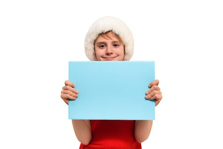 Cute boy in Santa hat with a blank blue board in his hands. Isolate on white Standard-Bild