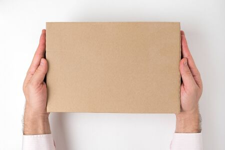 Rectangular cardboard box into mens hands on white background. Delivery service concept. Top view, mock up Banco de Imagens