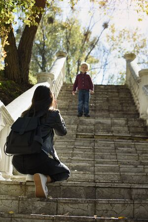 Mother and child on the stairs. Mom photographing son. Verrical frame. Zdjęcie Seryjne