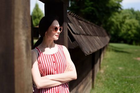Beautiful girl has rest in the village. Retro style. Young woman in the rays of the sun