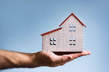 White wooden house on a male hand. White background. Housing concept
