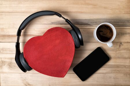 Red heart shape box with headphones, smartphone and coffee on wooden background. Music with love the concept Zdjęcie Seryjne
