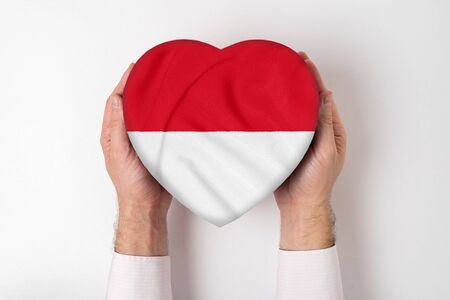 Flag of Monaco on a heart shaped box in a male hands. White background