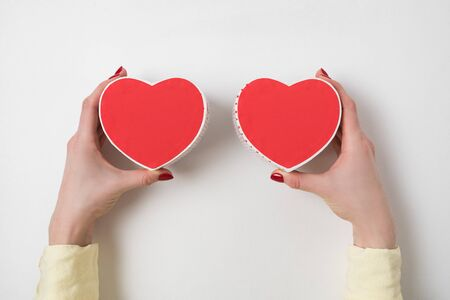 Two small red heart shaped boxes on female hands on white background. Gift for Valentines day.