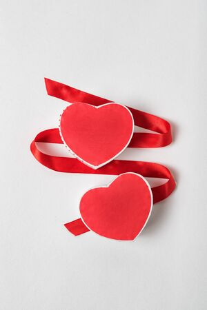 Two red heart-shaped boxes and satin ribbon on a white background. Symbol of love, Valentines Day. Banco de Imagens