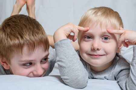Two boys lie and smiling. Brothers best friends. Fair-haired blonde boys. Portrait.