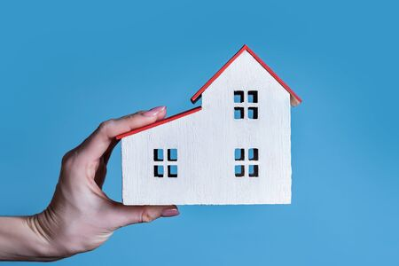 White wooden house in a female hand. Blue background. Housing concept