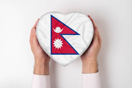 Flag of Nepal on a heart shaped box in a male hands. White background
