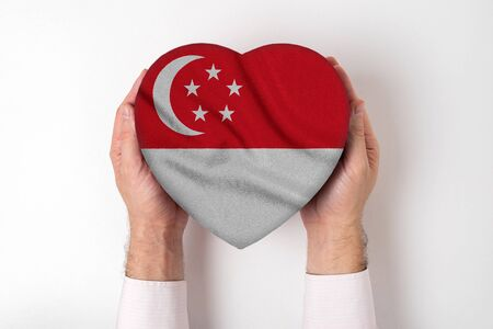 Flag of Singapore on a heart shaped box in a male hands. White background