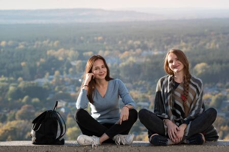 Two happy girls sitting on a background of nature. Stay with a friend, holidays vacation.