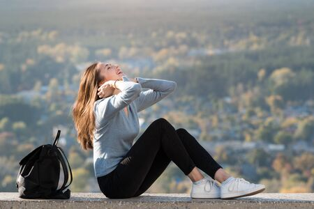 Young girl is sitting on top of a hill and looks at sky. Front view