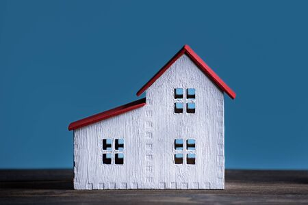 House model on blue background. Home construction concept. Front view closeup.