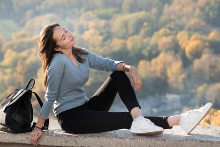 Beautiful girl enjoys nature sitting on a hill with closed eyes. Sunny day