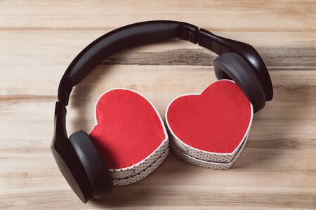 Headphones and two gift boxes in the shape of a heart. Music of hearts. Top view