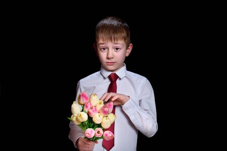 Cute boy in white shirt with a bouquet of tulips. Isolate on black background