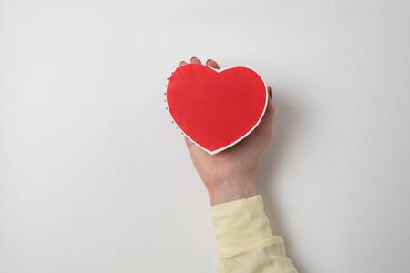 Small red heart shaped box on female palm isolated on white background.