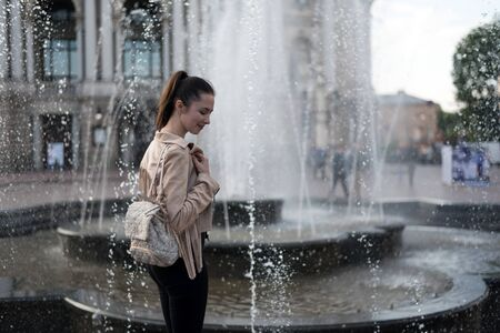 Girl standing near the fountain. Weekend in Europe. A spray of water
