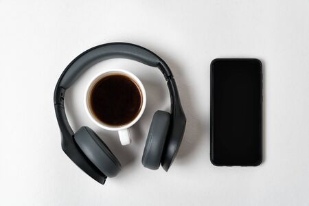Wireless full-size headphones, smartphone and cup of coffee on white background. Directly above.