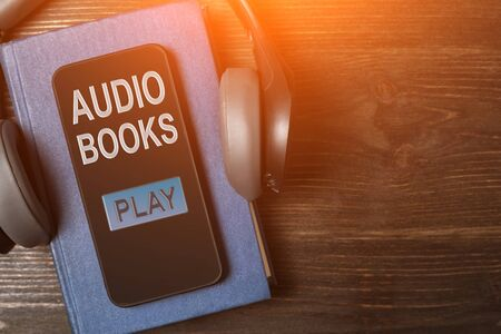 Smartphone on the book with headphones. Audiobook concept. Dark wooden background. Top view. Zdjęcie Seryjne