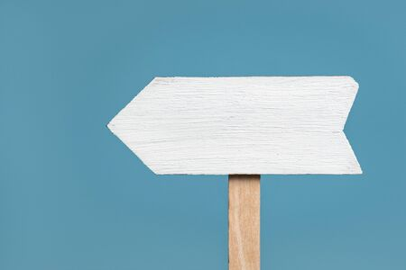 Wooden signpost on blue background. Arrow pointer. Front view, closeup. Zdjęcie Seryjne
