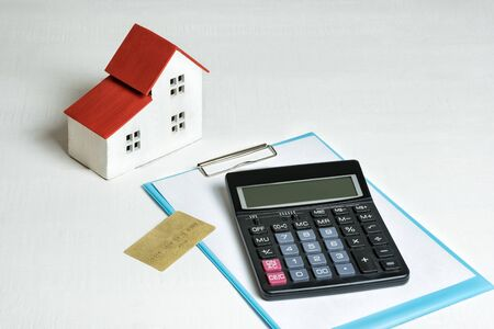Model of house, credit card and calculator on white background. Buying a home. Concept of mortgage and real estate..