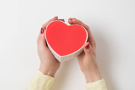 Vintage style red heart shaped box in female hand isolated on white background. Banco de Imagens