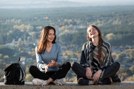 Two happy girls sitting on background of nature. Front view. Friendship. Imagens