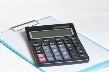 Documents and calculator on a white background. Financial report, annual budget concept. Imagens