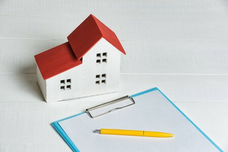 House model, papers and calculator on white background. Buying home rental agreement concept.