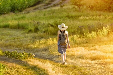 Young woman in hat walks through meadow. Walk on a sunny day. Back view.