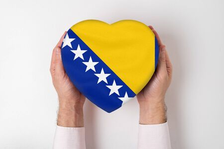Flag of Bosnia and Herzegovina on a heart shaped box in a male hands. White background