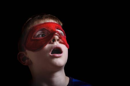 Boy in red carnival mask on black background. Surprise and admiration. Portrait closeup isolated