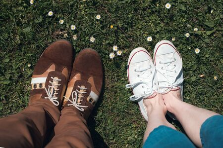 Male and female feet in sneakers on a grass, first person. Couple relaxing on the lawn. Top view.