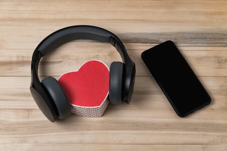 Full-size wireless headphones pulled over small red heart-shaped box and smartphone on light brown wooden table. Imagens