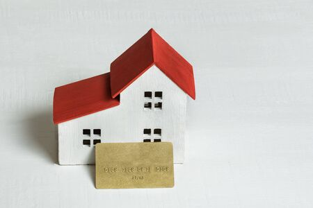 House and credit card on white background. Buying a home, real estate and mortgage concept