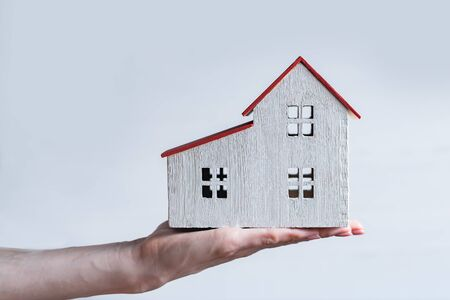 White wooden house on a female hand. White background. Housing concept