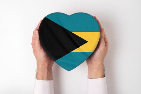 Flag of Bahamas on a heart shaped box in a male hands. White background