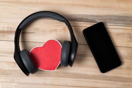 Full-size wireless headphones pulled over small red heart-shaped box and smartphone on light brown wooden table. Directly above.