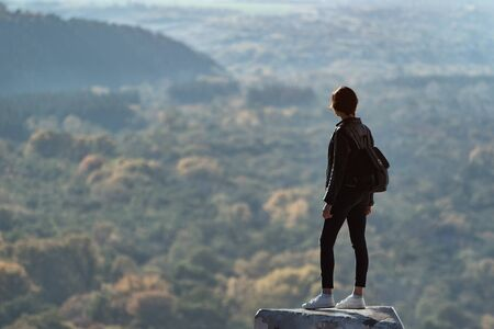 Girl stands on a hill and looks into the distance of the forest.