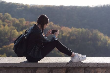 Young woman sits on the background of nature and making photo on phone. Photos of nature on smartphone