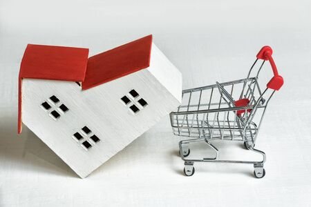 Model of house and basket on white background. Buying a house. Real estate and mortgage concept Imagens