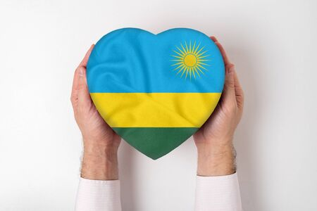 Flag of Rwanda on a heart shaped box in a male hands. White background Imagens