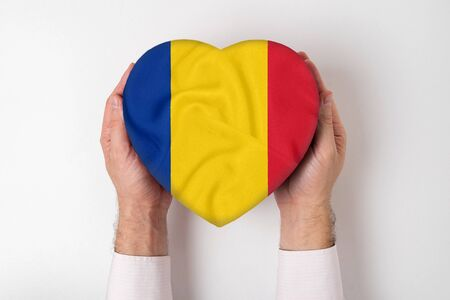 Flag of Romania on a heart shaped box in a male hands. White background
