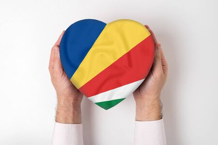Flag of Seychelles on a heart shaped box in a male hands. White background