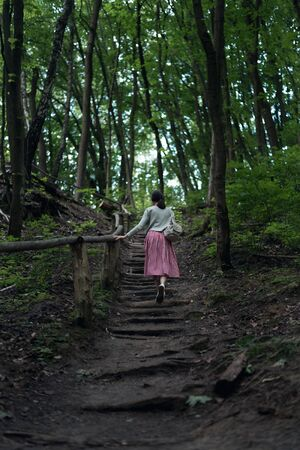 Young woman goes in forest alone. Girl walks in wild park. Back view