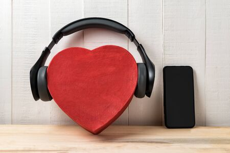 Full-size wireless headphones pulled over red heart-shaped box and smartphone. Front view Imagens