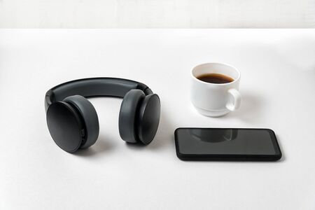 Wireless full-size headphones, smartphone and cup of coffee on white background Imagens