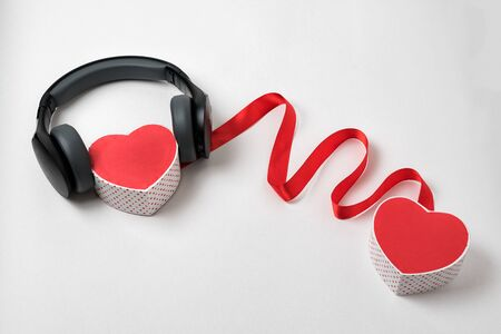 Two heart shape boxs, red ribbon and headphones on a white background. Connection hearts Imagens