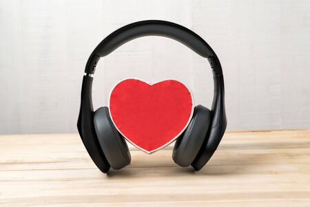 Wireless full-size headphones wearing small red heart-shaped box. Love music concept. Front view.